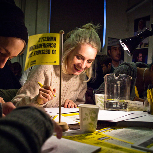 Image of people writing letters at Amnesty International Netherlands